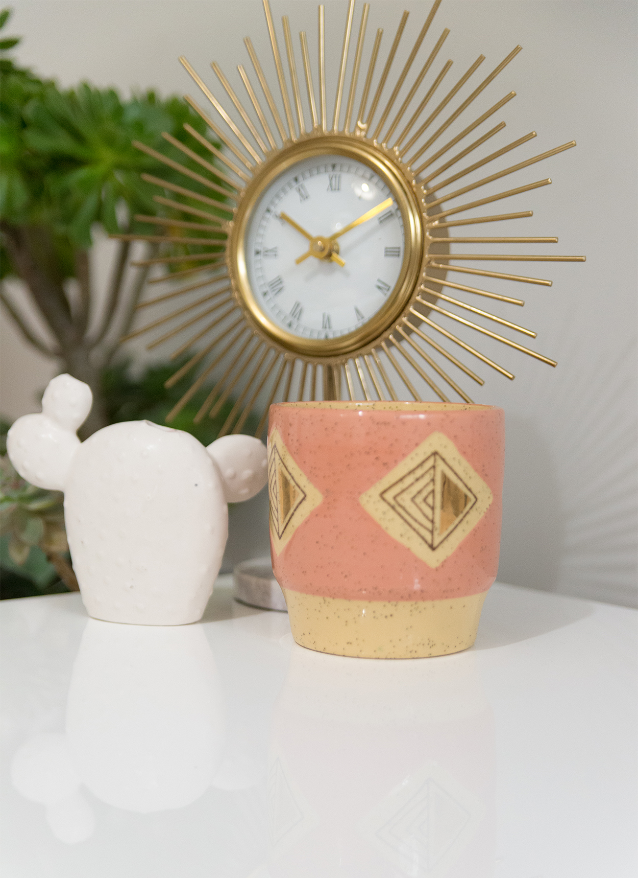 gold sunburst clock with a pink ceramic cup and a ceramic cactus sitting on the table