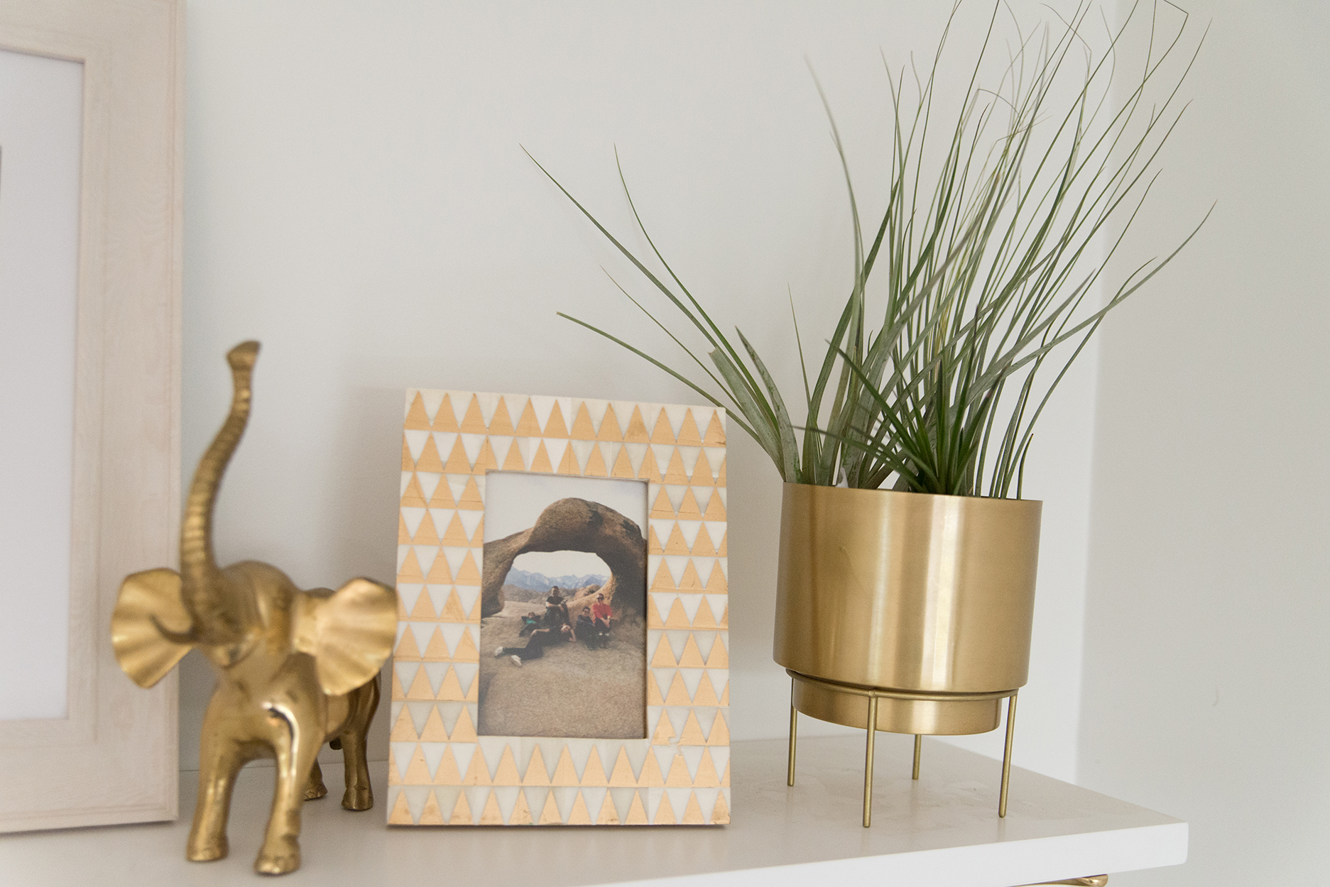 a white shelf with a plant potted in a gold pot, a dessert pic in a geometric printed frame and a gold elephant sculpture