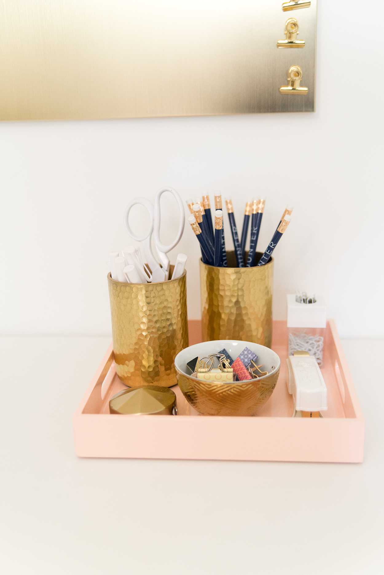 a pink tray holding a gold bowl of clips, and two gold cups holding pencils and scissors