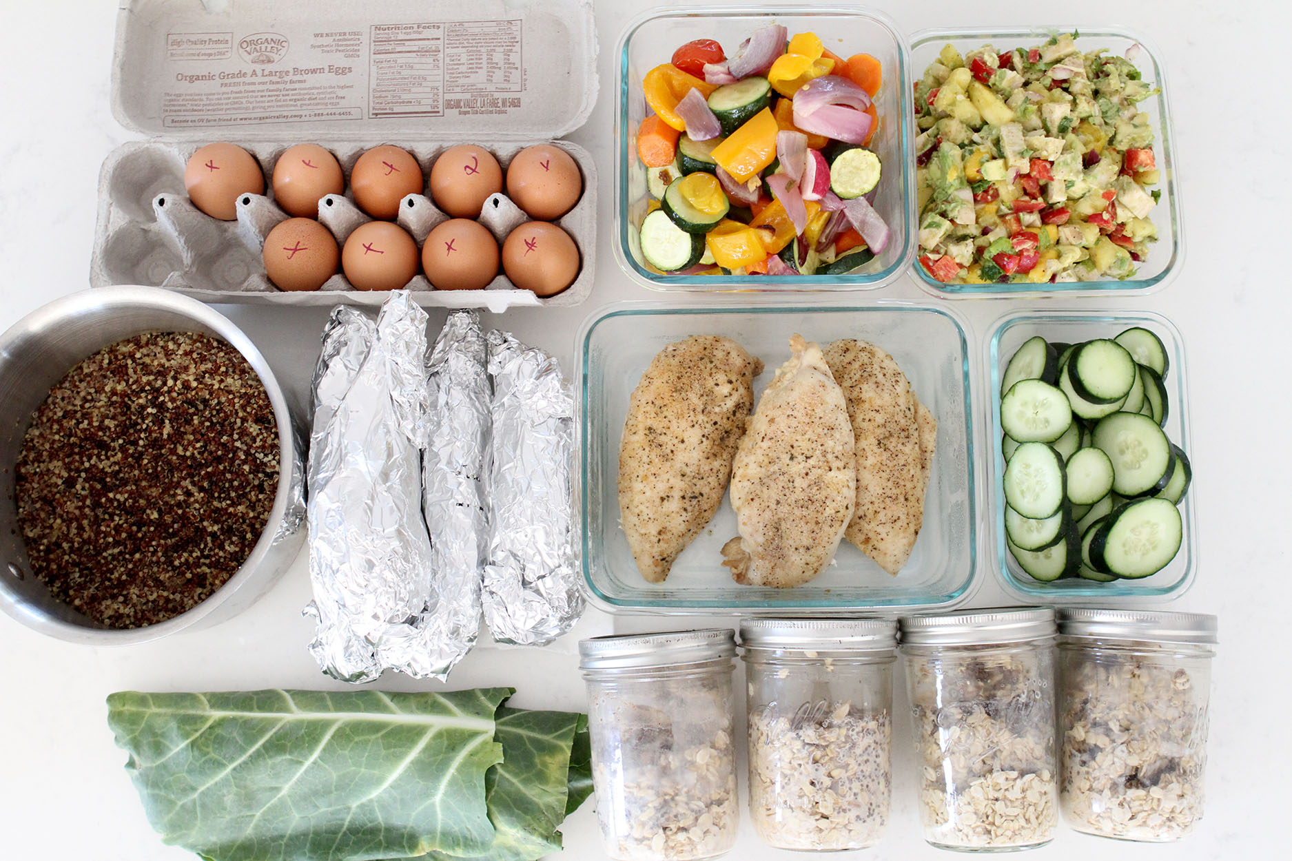 meal prep with hard boiled eggs, sauteed veggies, kale, chicken, cucumbers and chia seeds