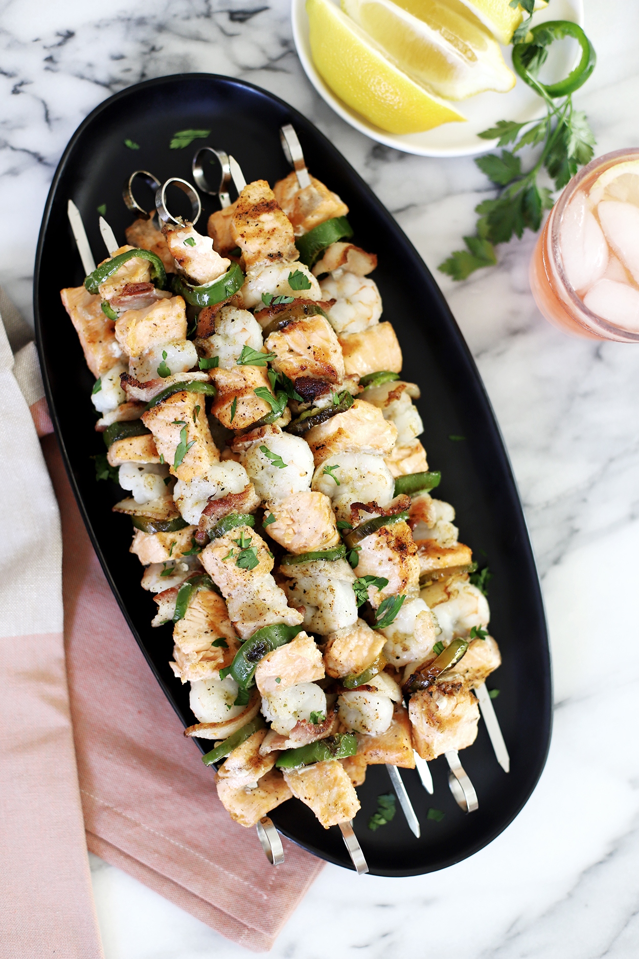 overhead picture of shrimp and salmon skewers on a black plate