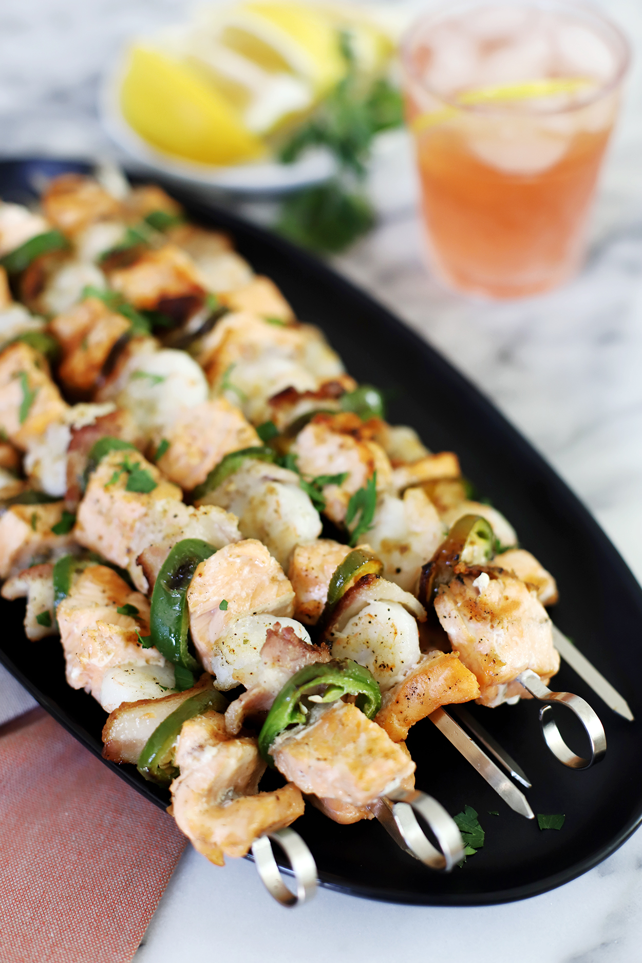 salmon and shrimp skewers on a black plate with lemons and a pink drink in the background