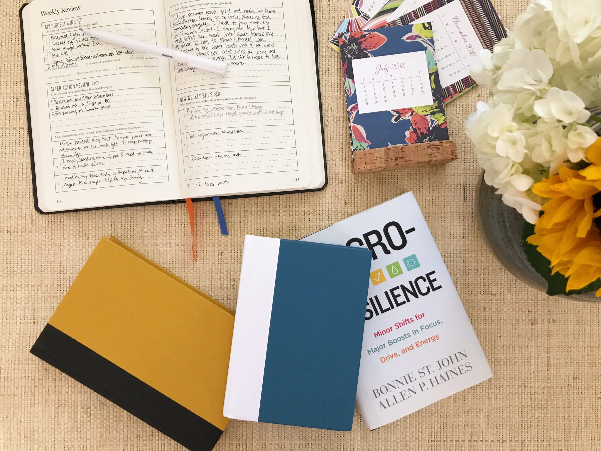 books scattered on a table with a calendar and a flower arrangement