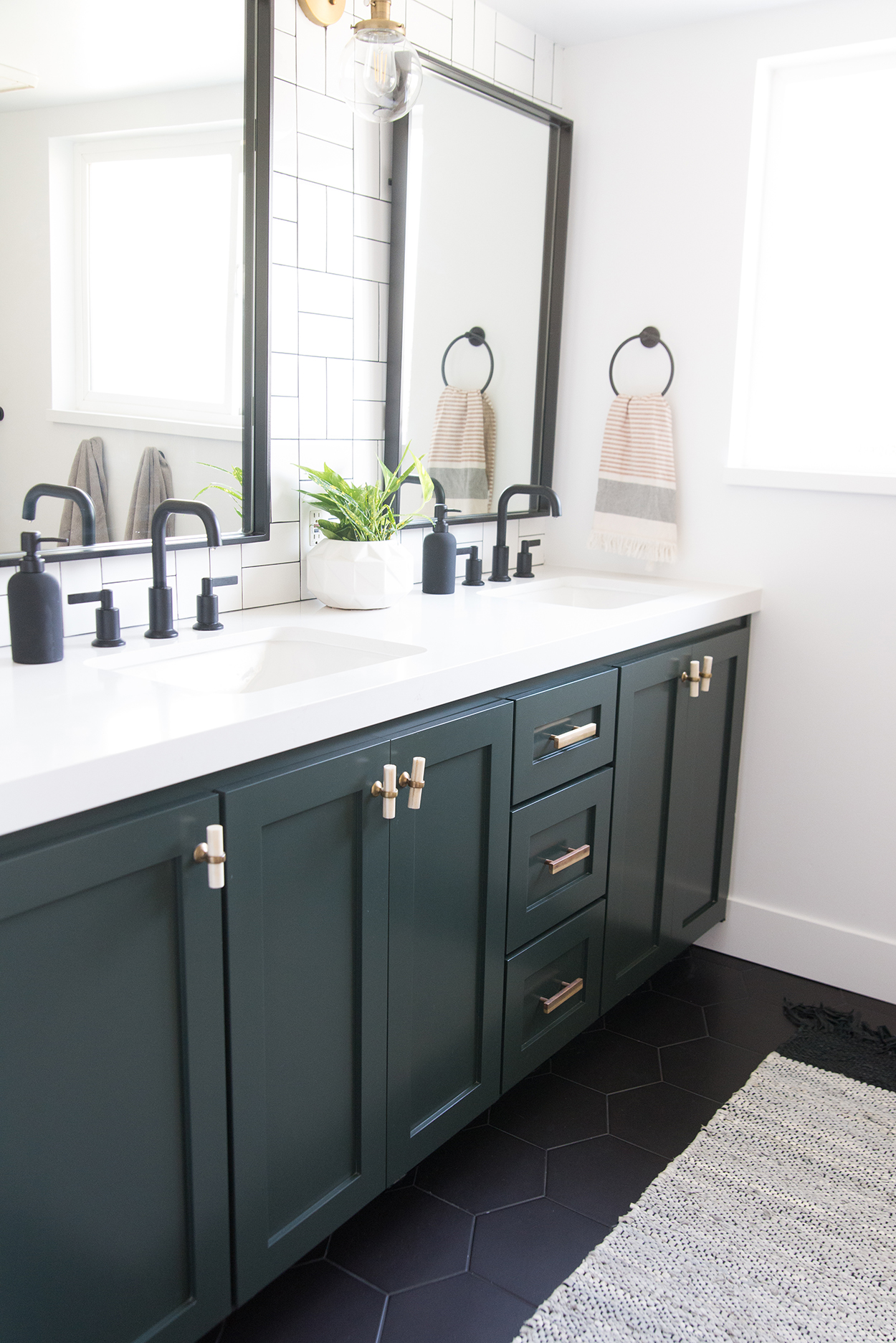 A black bathroom vanity with a white coutertop and black fixtures