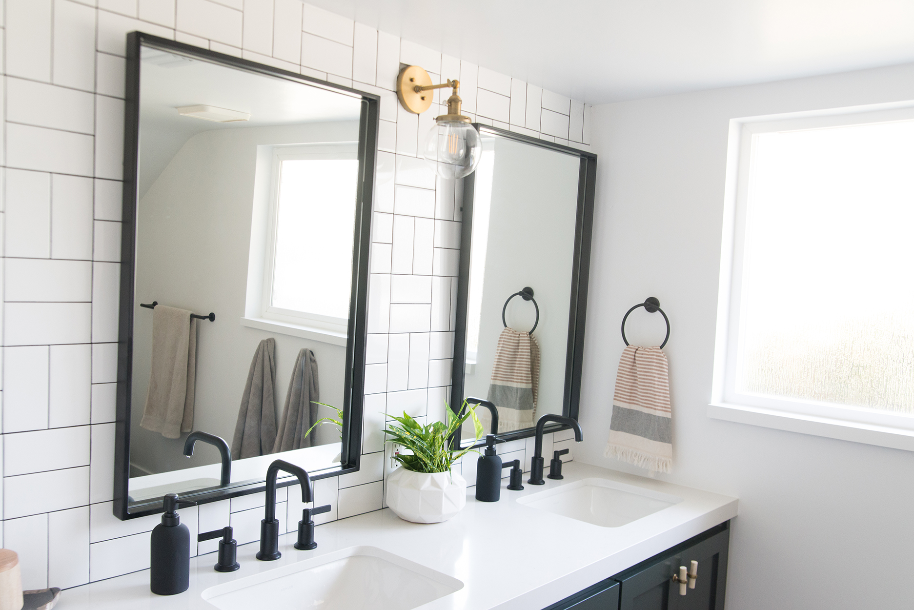 Bathroom mirrors with a white vanity counter top and black fixtures