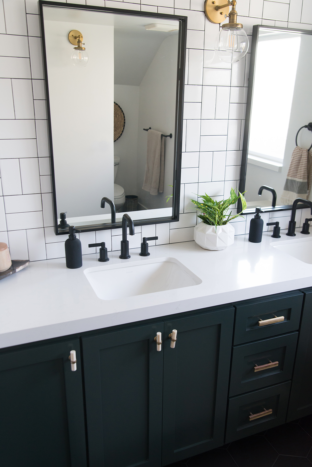 white and black tiled bathroom wall with a black mirrors and a black vanity with a white counter