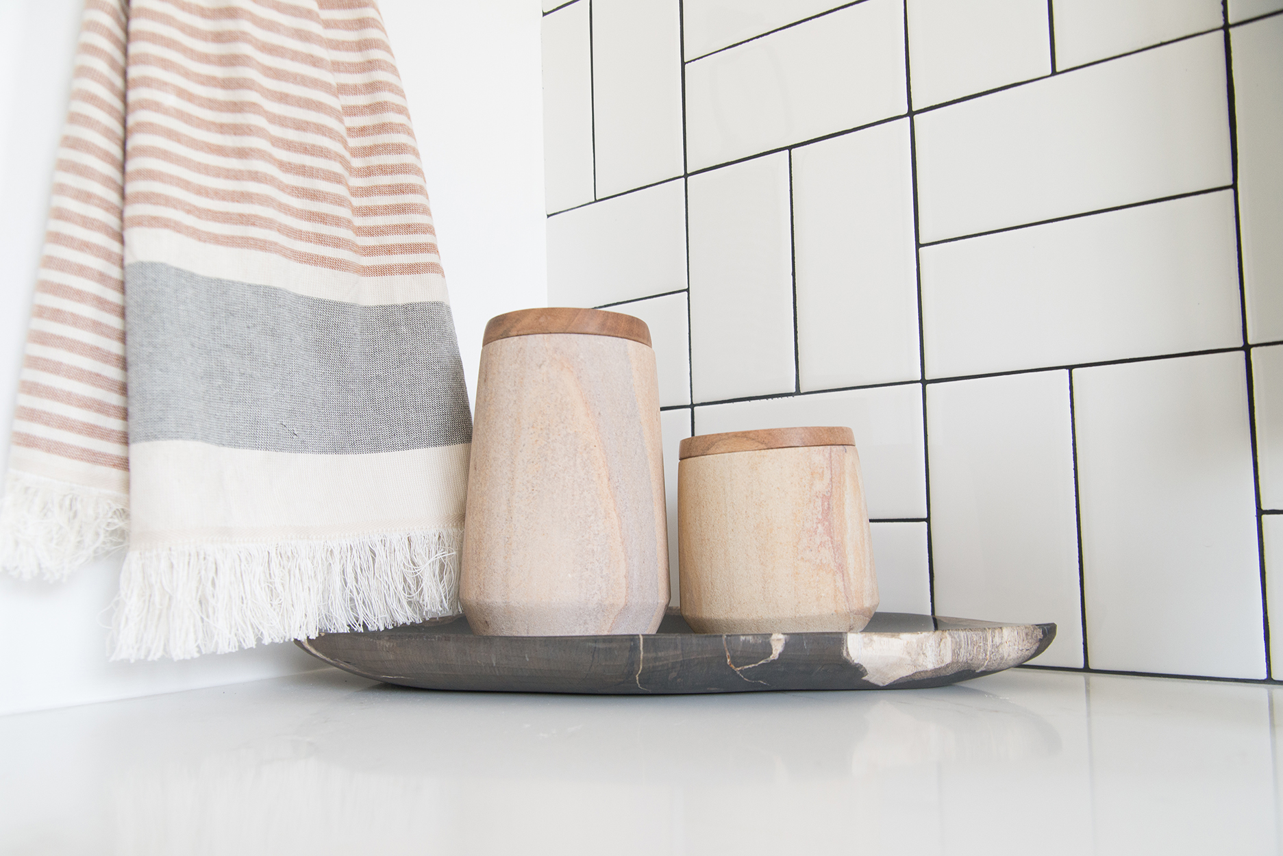 white tiled wall, a towel hanging and a cup and toothbrush holder