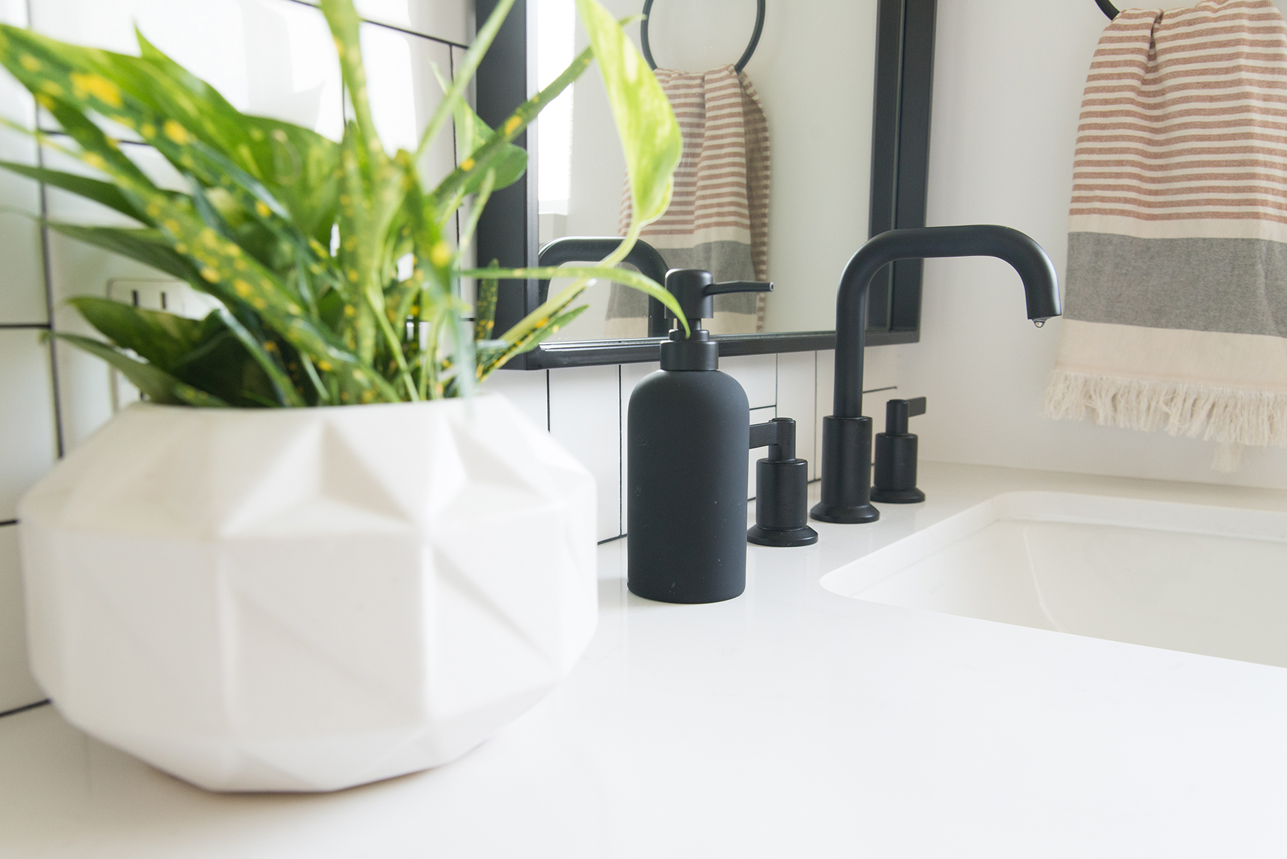 white bathroom vanity counter top with black fixtures and a white vase with a green plant