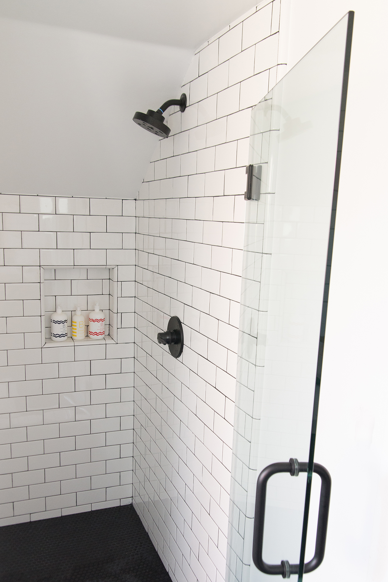 shower with a glass door and white tile and a black tile floor