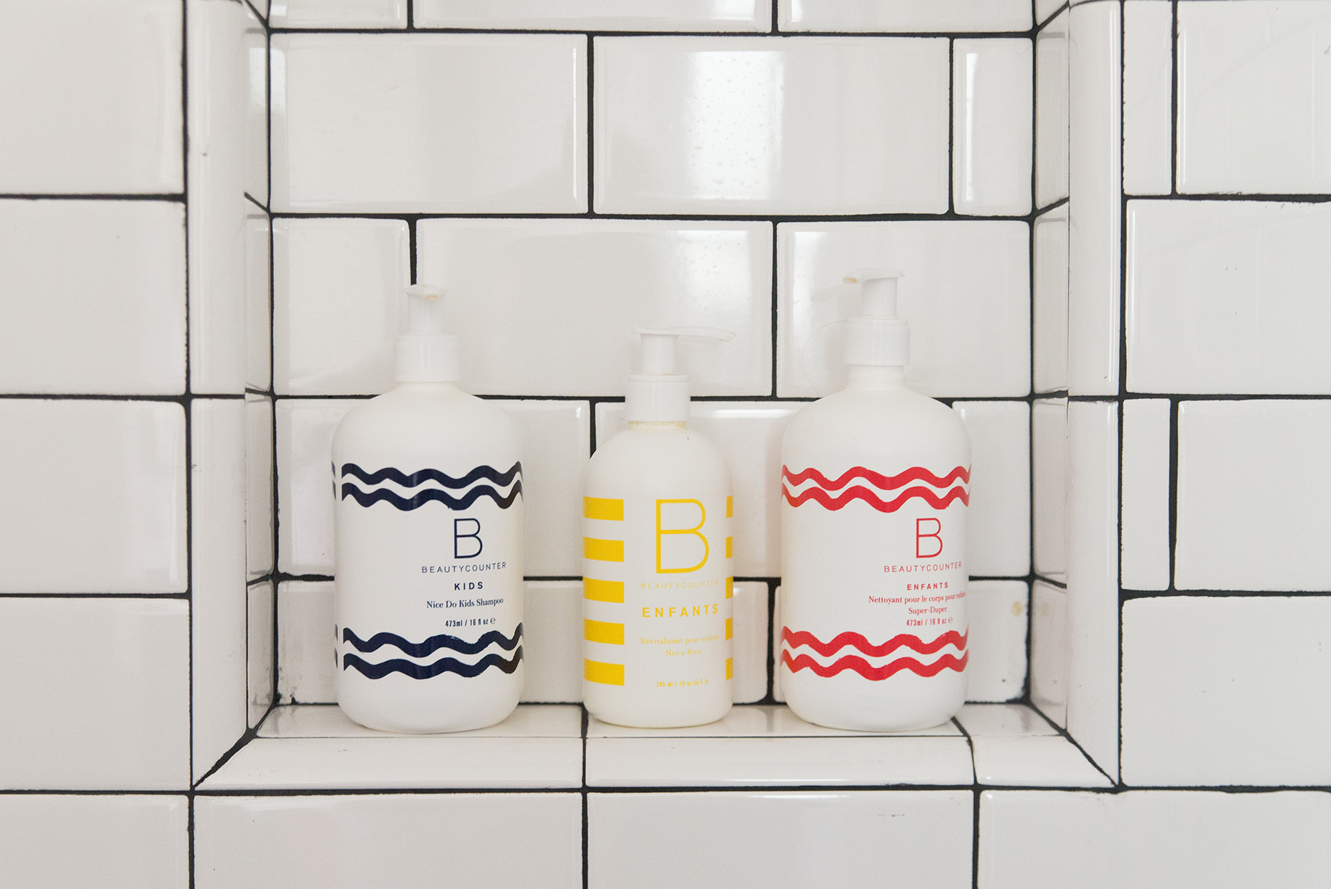 beauty counter shampoo and body soap in a white tiled shower