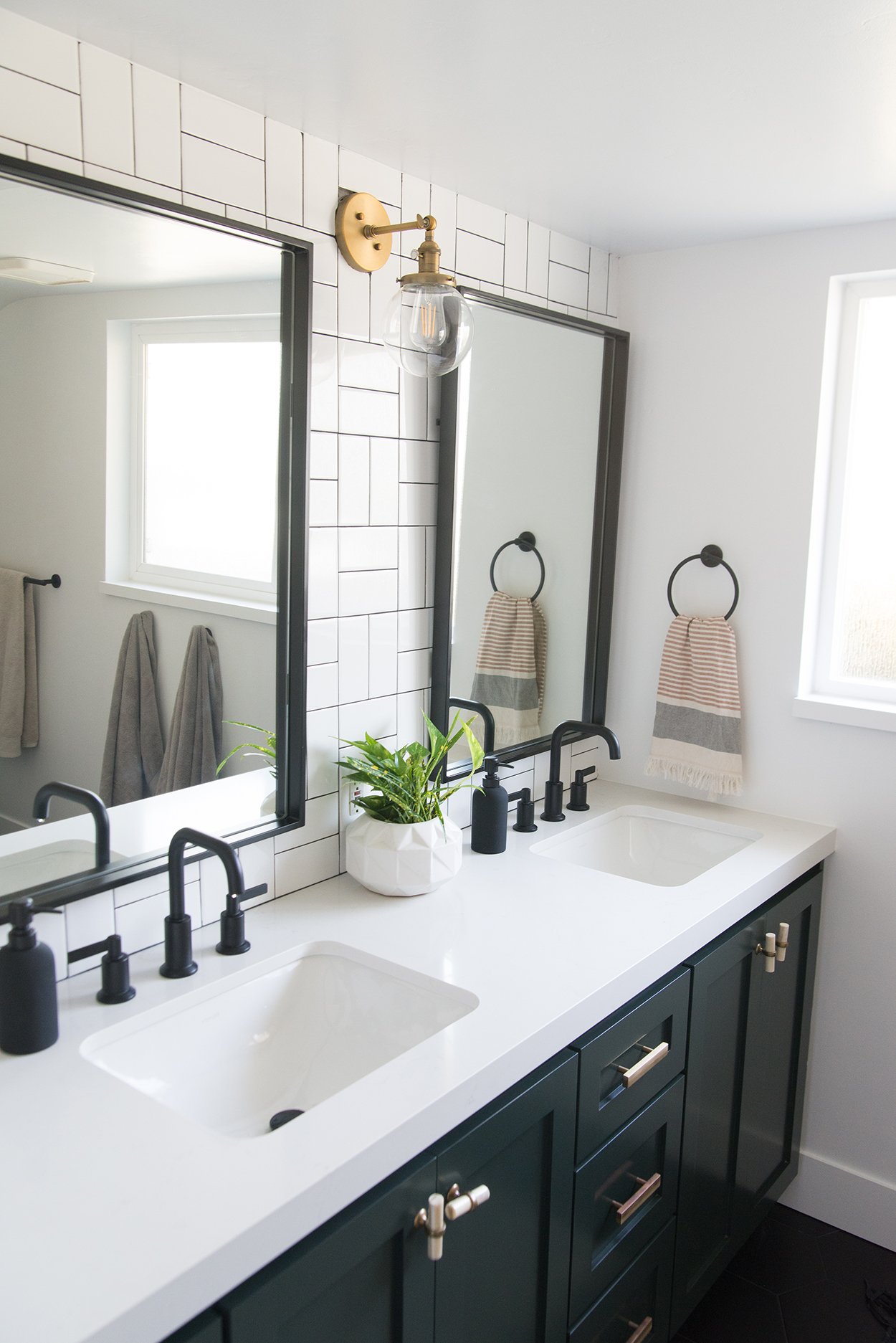 black bathroom vanity with a white counter top and black fixtures, black mirrors and a white tiled wall