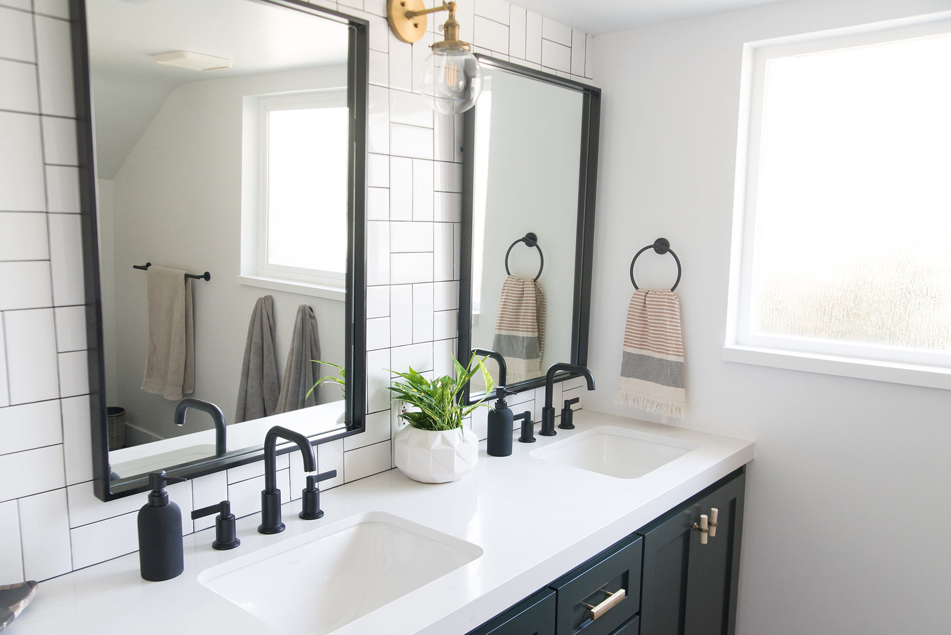 white counter top with black fixtures and black mirrors on a white tiled wall