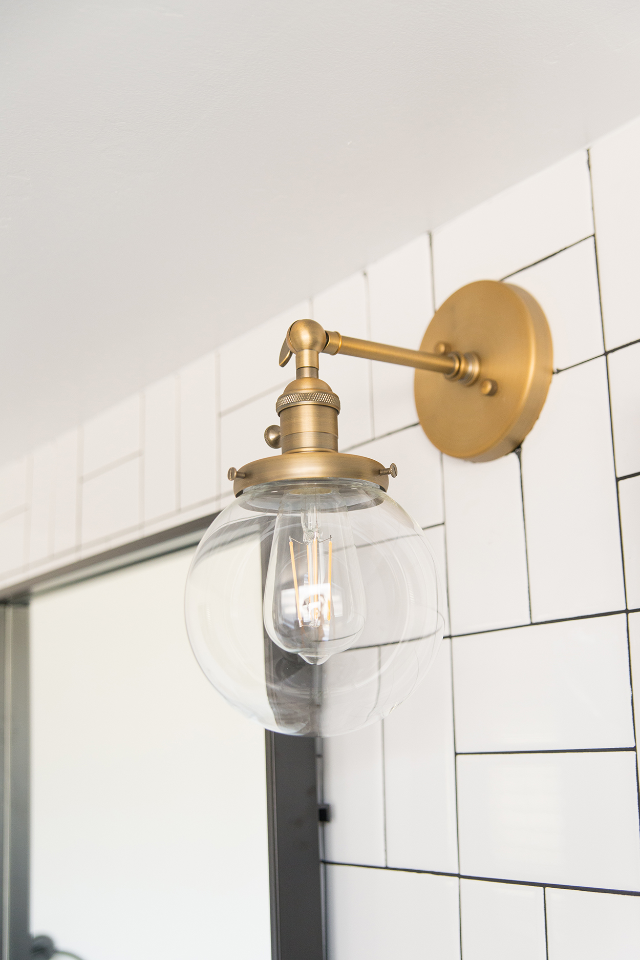 Antique brass light fixture with globe glass and an Edison bulb on a white tiled wall