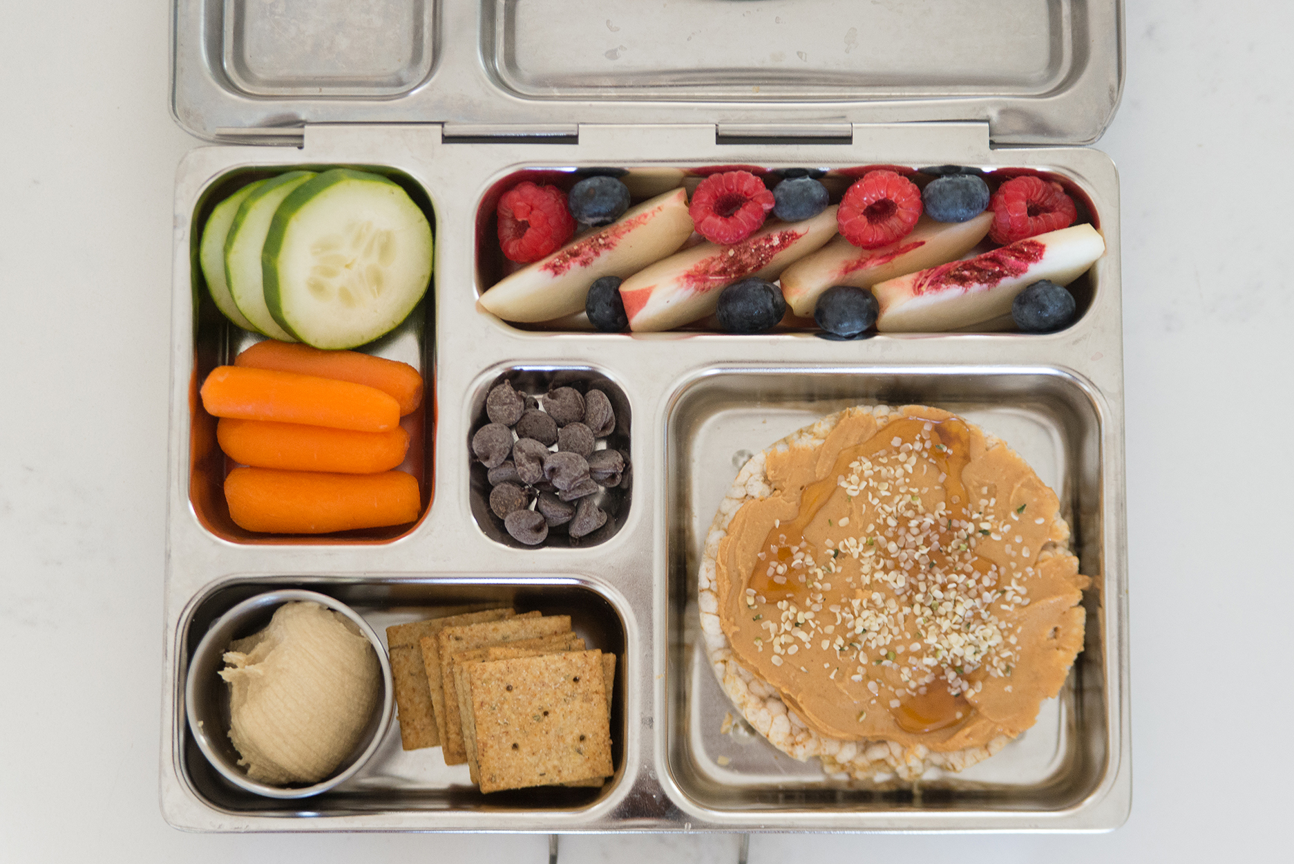 bento box full of fruit, veggies, hummus and a peanut butter rice cake