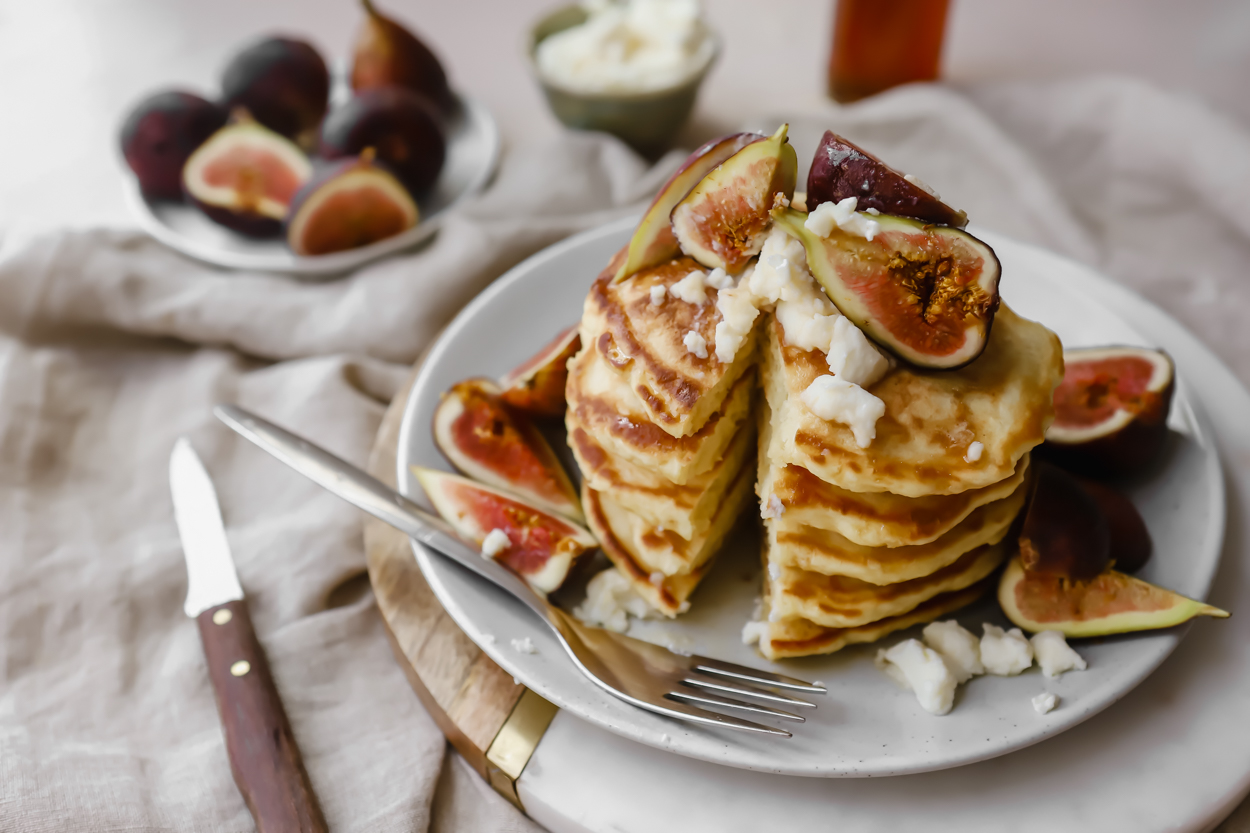 A stack of fluffy pancakes with a slice taken out, a knife to the side, and a plate of fresh figs and honey in the background