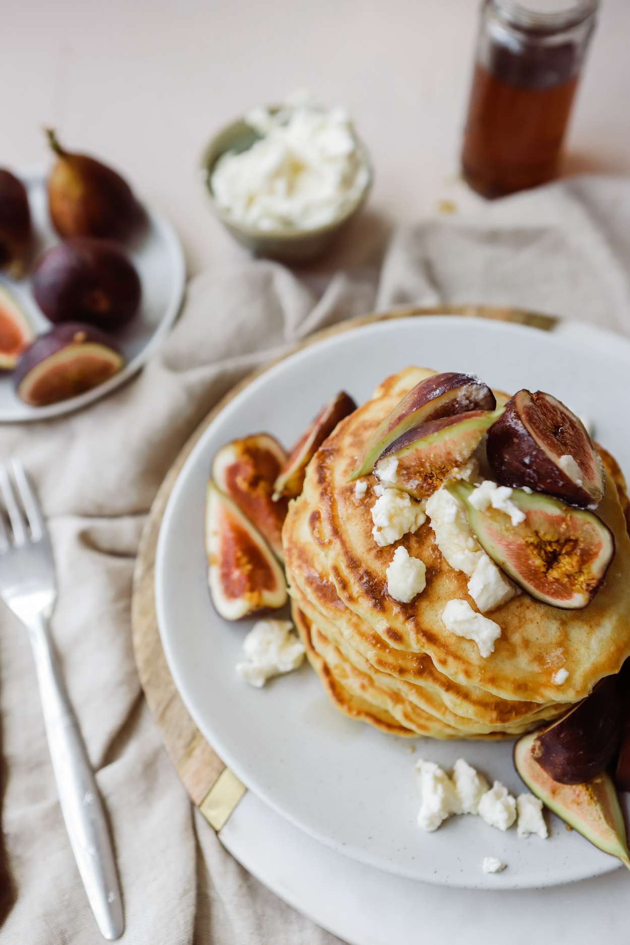 A stack of pancakes on a white plate topped with fresh figs and ricotta cheese, drizzled with honey