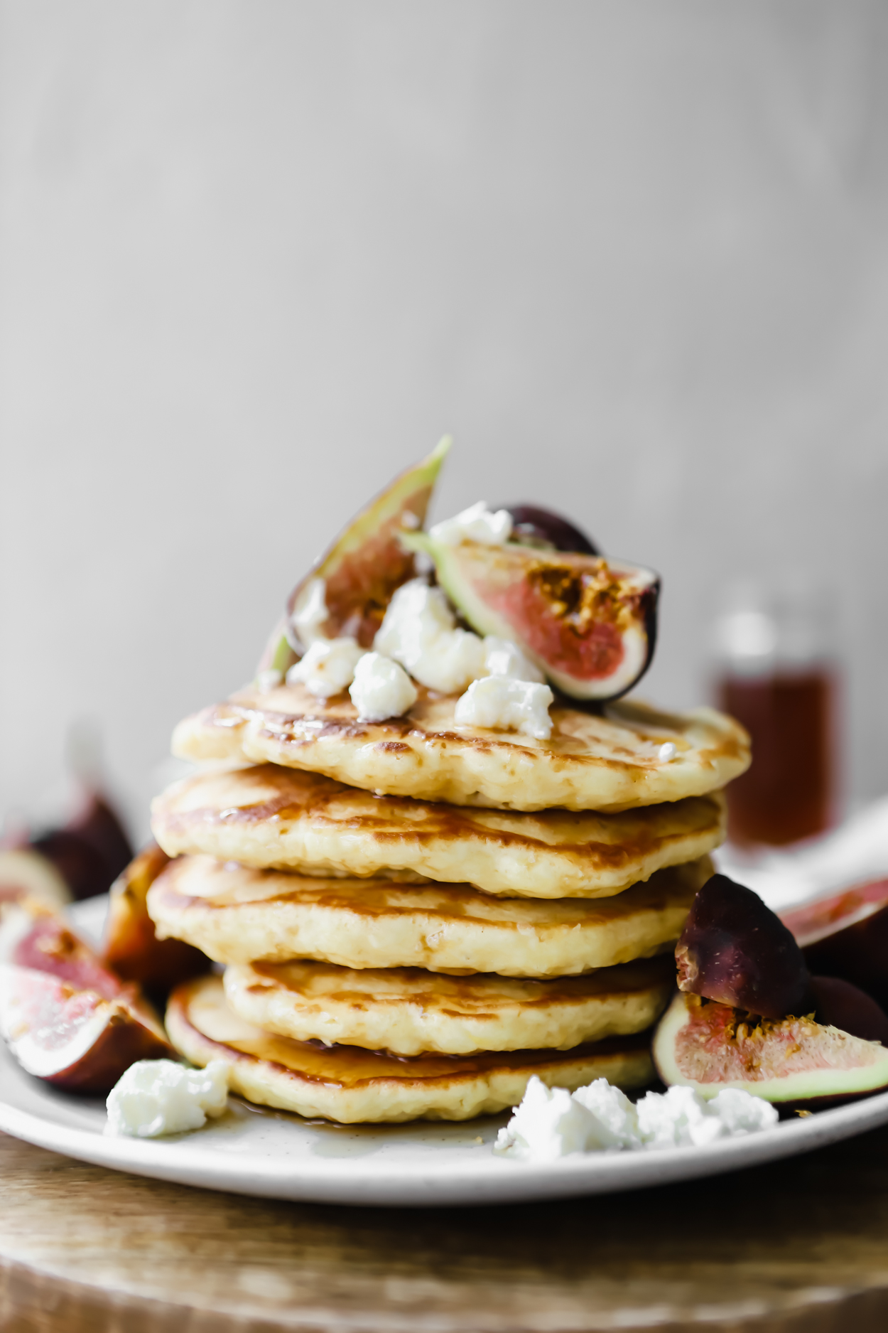 A stack of fluffy pancakes on a plate with fresh figs and ricotta cheese
