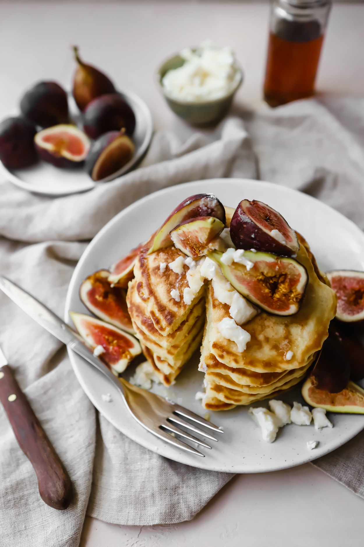 A stack of fluffy pancakes topped with fresh figs and ricotta cheese, with a slice cut out