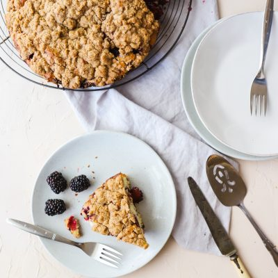 Slice of Blackberry Cake on a gray plate with a fork on a white background