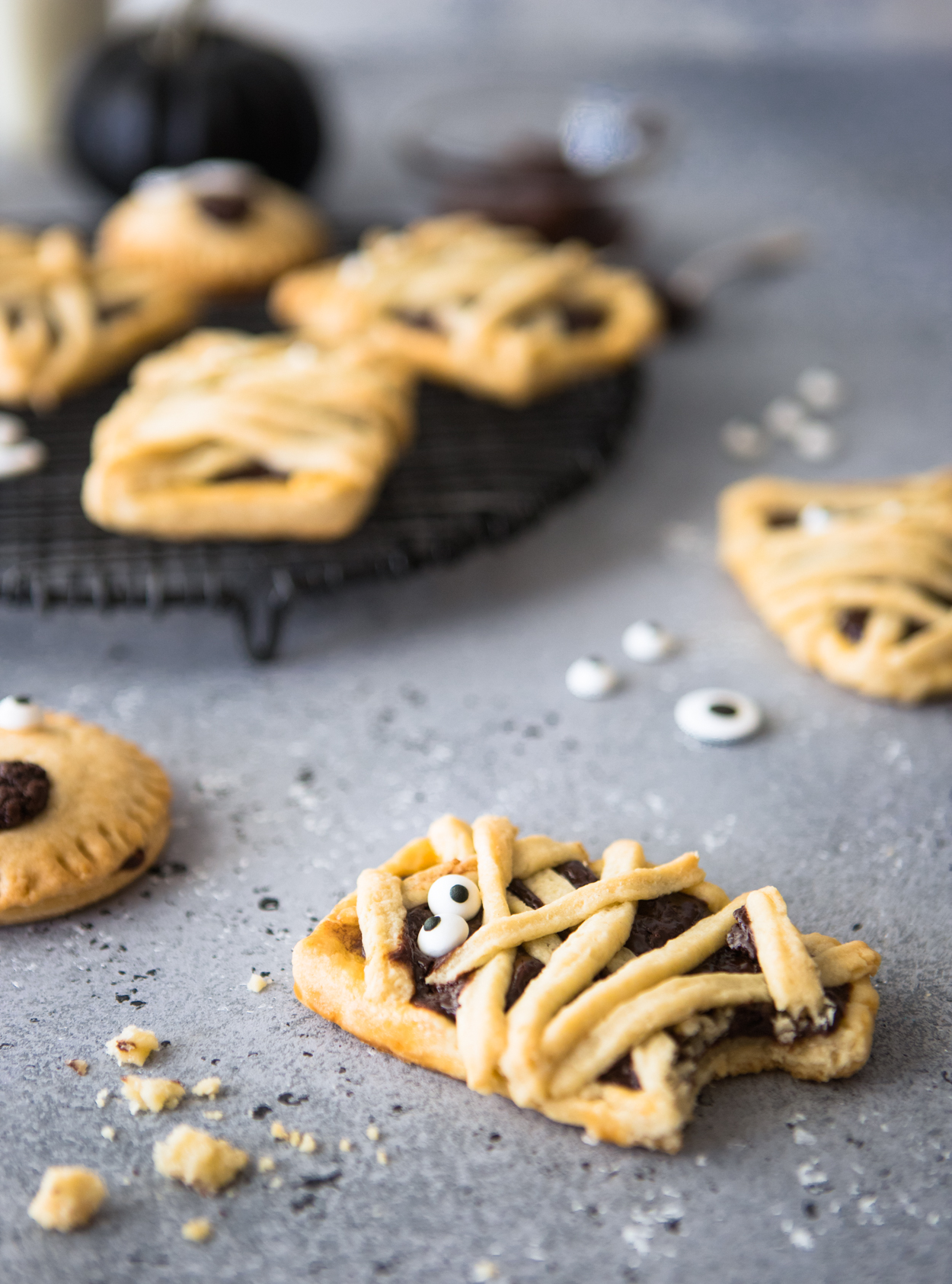 Mummy decorated chocolate hand pies against a gray backdrop