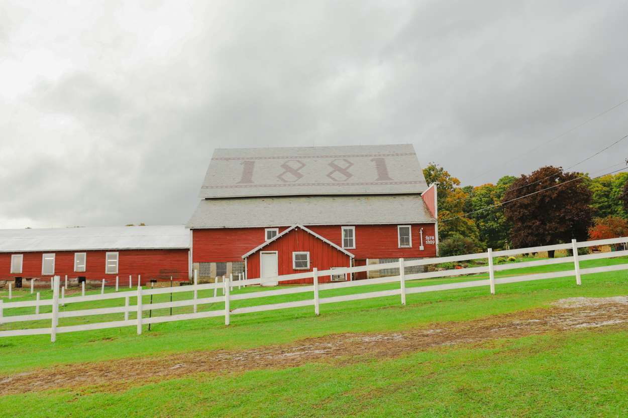 Red barn with tiled roof marked 1881 in green field with white wooden fence in Vermont