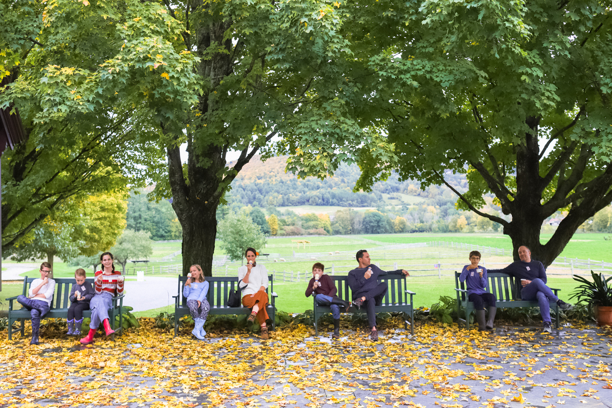 Group of people sitting on benches eating ice cream in front of green trees and yellow leaves