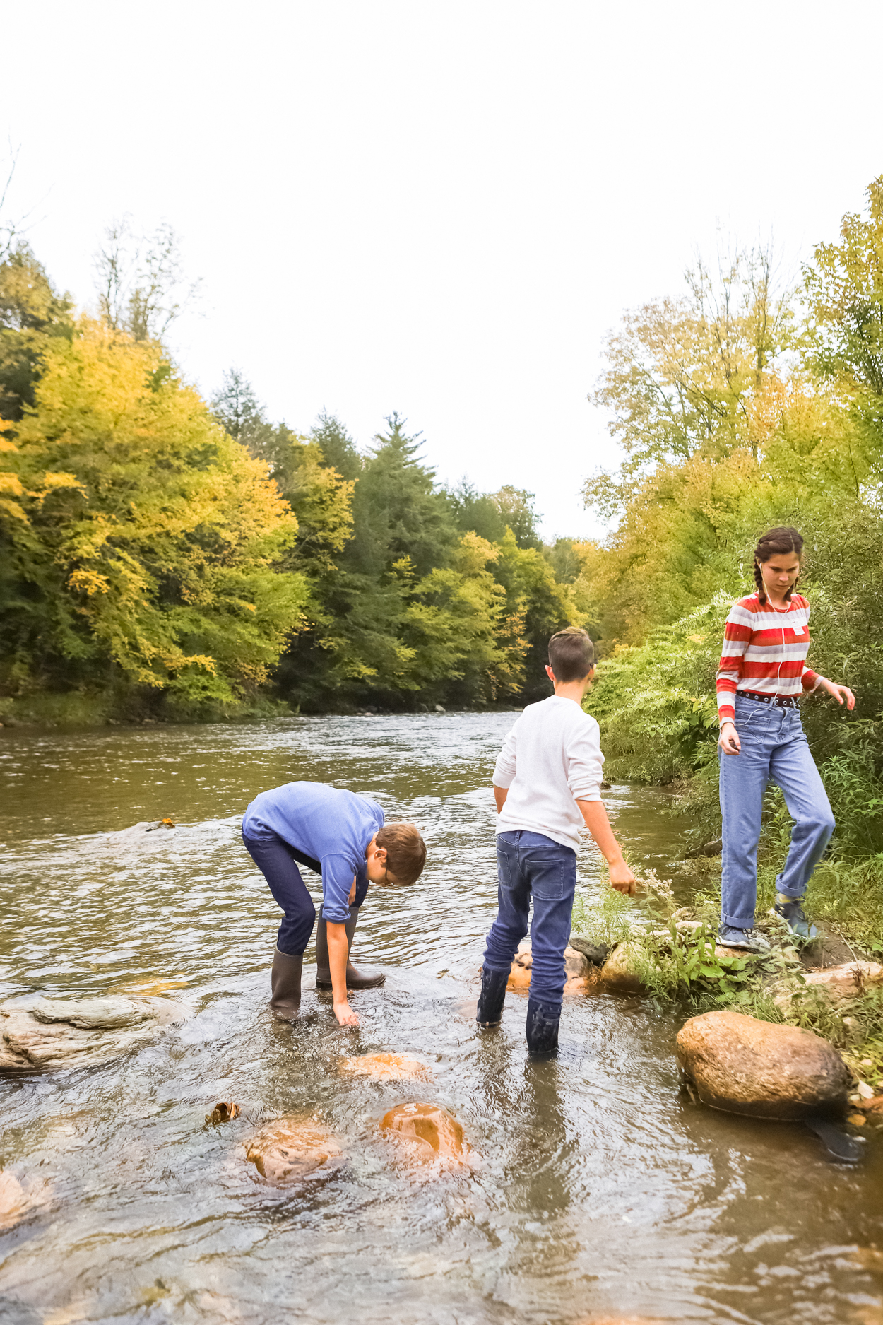 Kids playing in Ottauquechee River during the Fall in Vermont