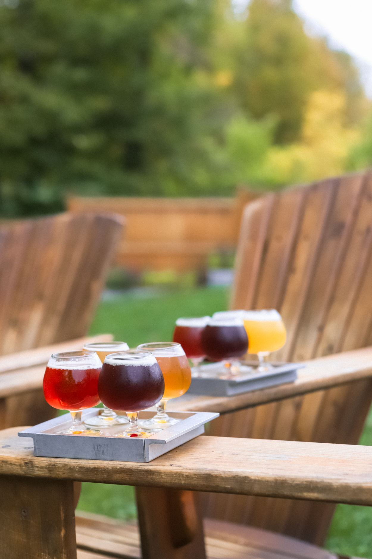 Flight of craft beers on a metal tray on wooden Adirondack chairs at a brewery in Vermont