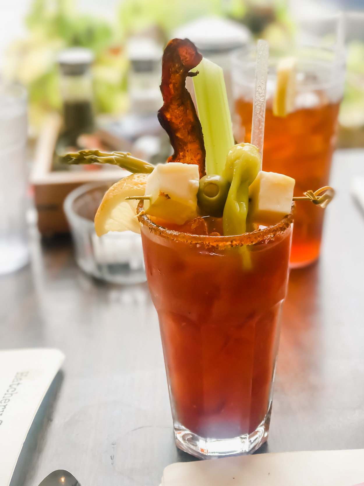 Bloody Mary Drink with bacon, asparagus, olive and cheese garnish on a table at Hatchery Restaurant in Ludlow Vermont