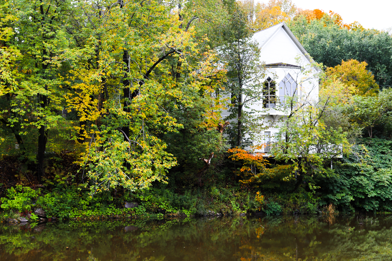 White farmhouse on the sore of a river in Vermont during the Fall