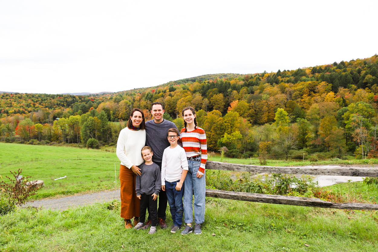 Family standing in front of Green Mountains at Sugarbush Farm in Woodstock Vermont in the Fall