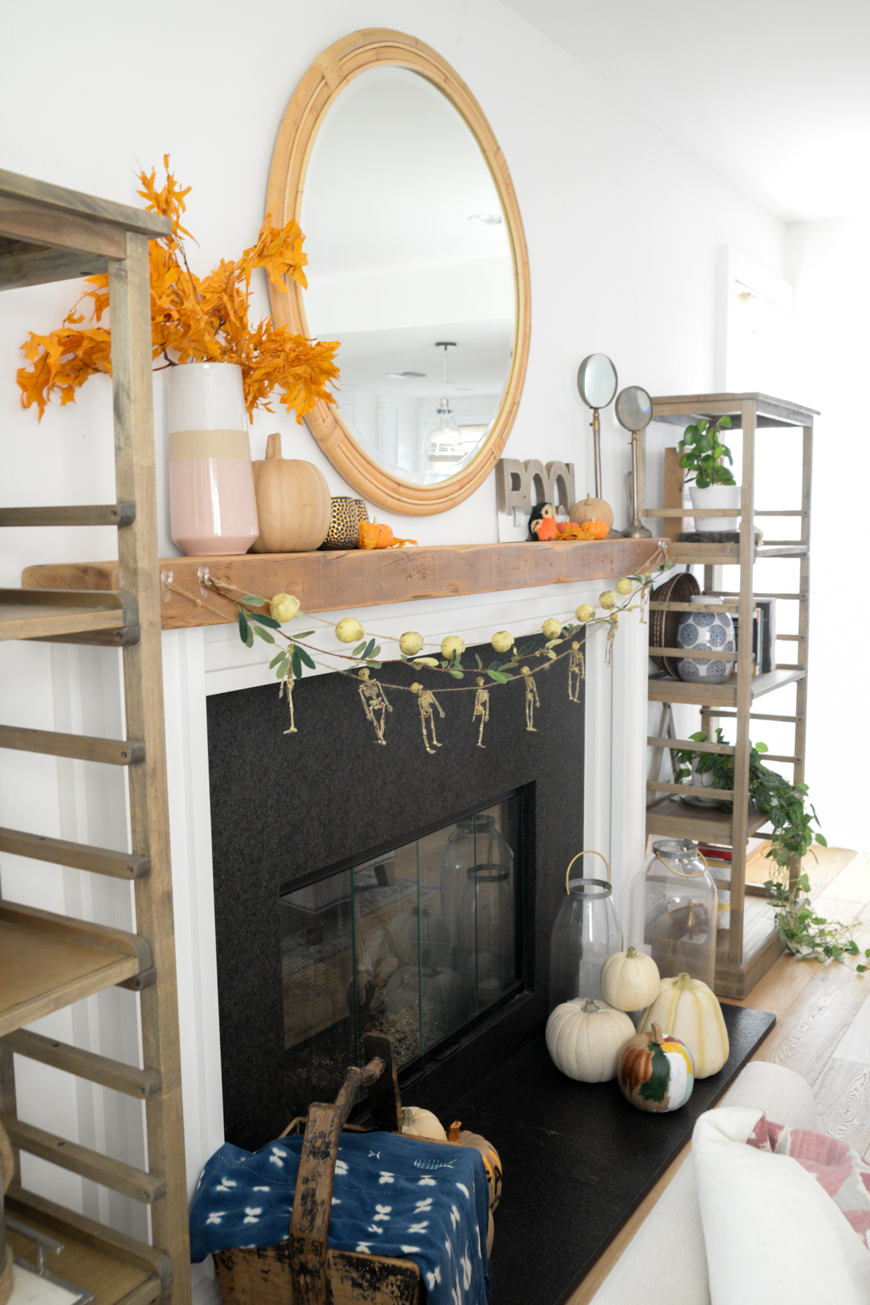 Skull and skeleton garland hanging from a wood beamed mantel with orange leaves and pumpkins and round mirror