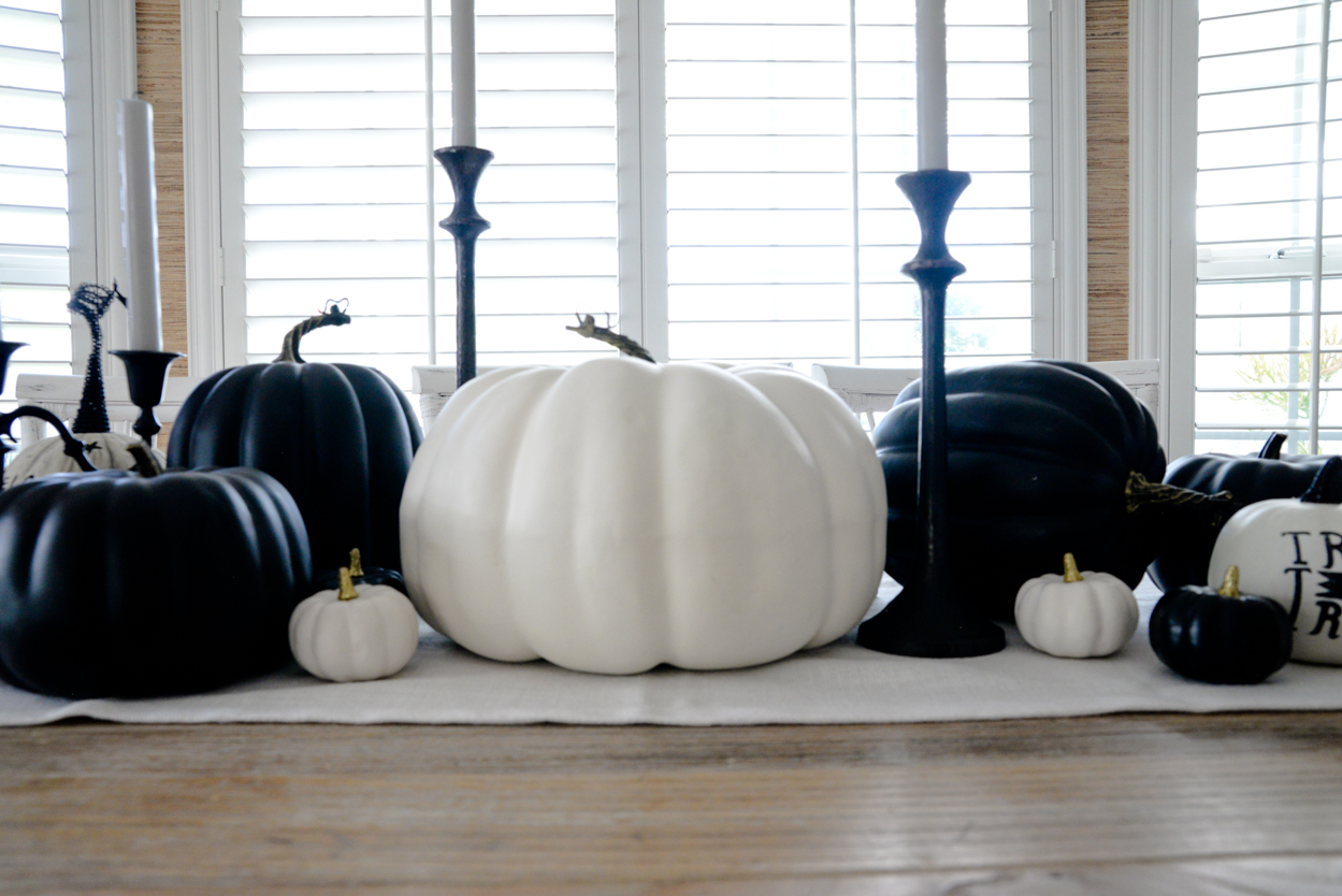 Black and white pumpkins and black candlesticks sitting on a rustic wood farmhouse dining table