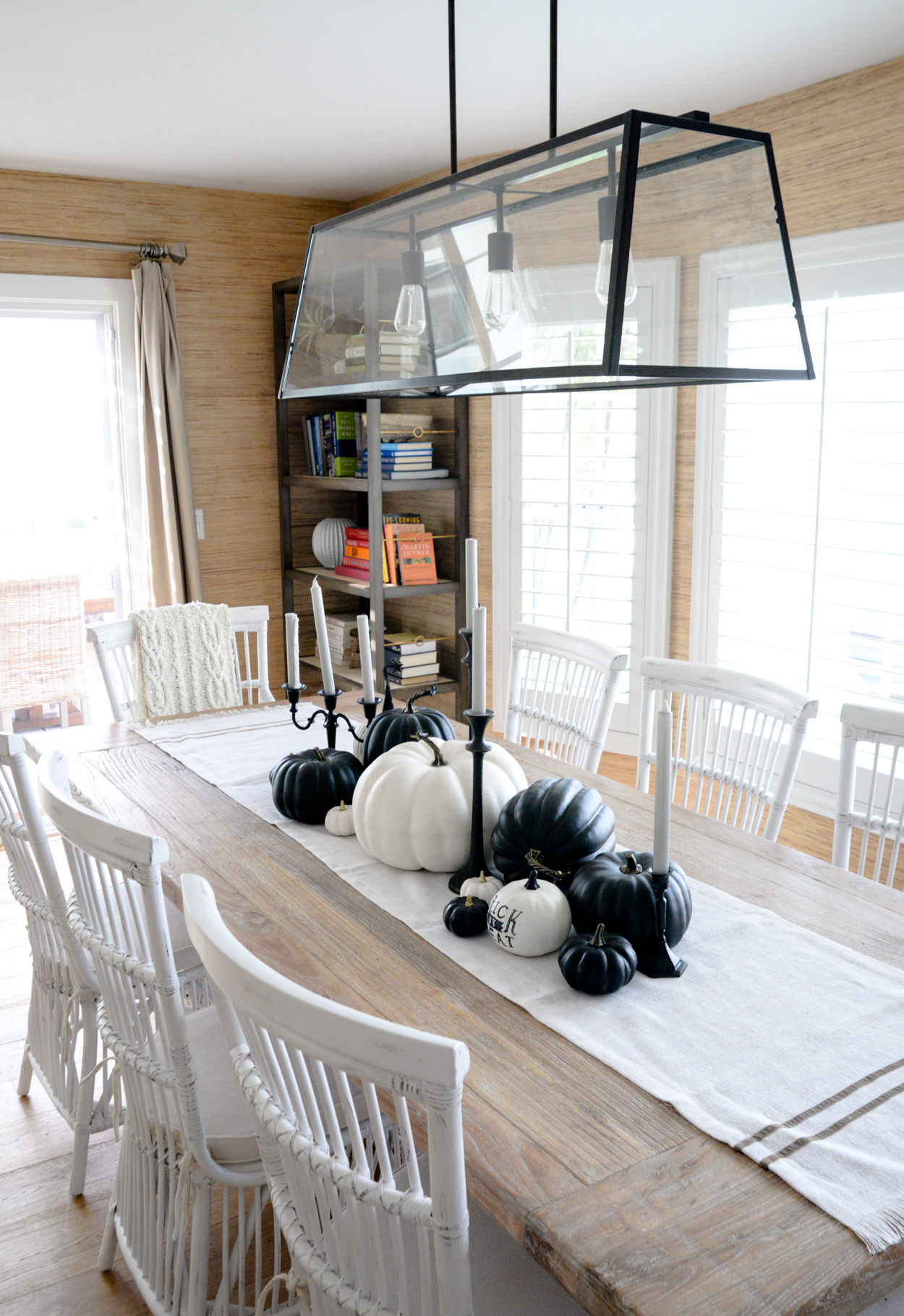 Black and white pumpkins sitting on a rustic wood dining table with white chairs and black candlesticks