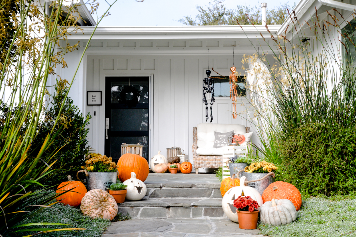 decorative pumpkins and mums and lanterns on a slate porch in a front yard