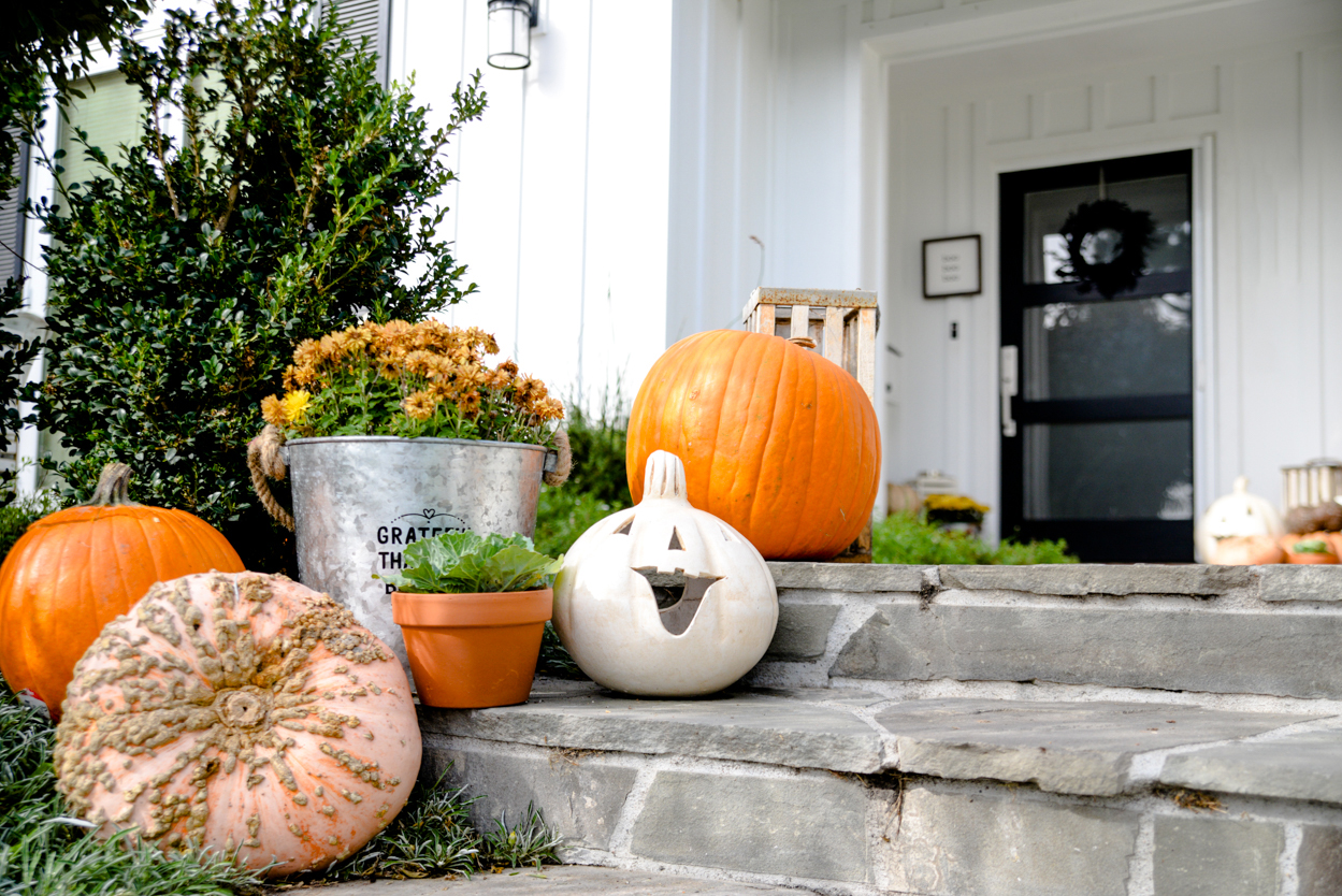 Decorate orange pumpkins and mums in a zinc tin and ornamental cabbage on a slate porch with steps