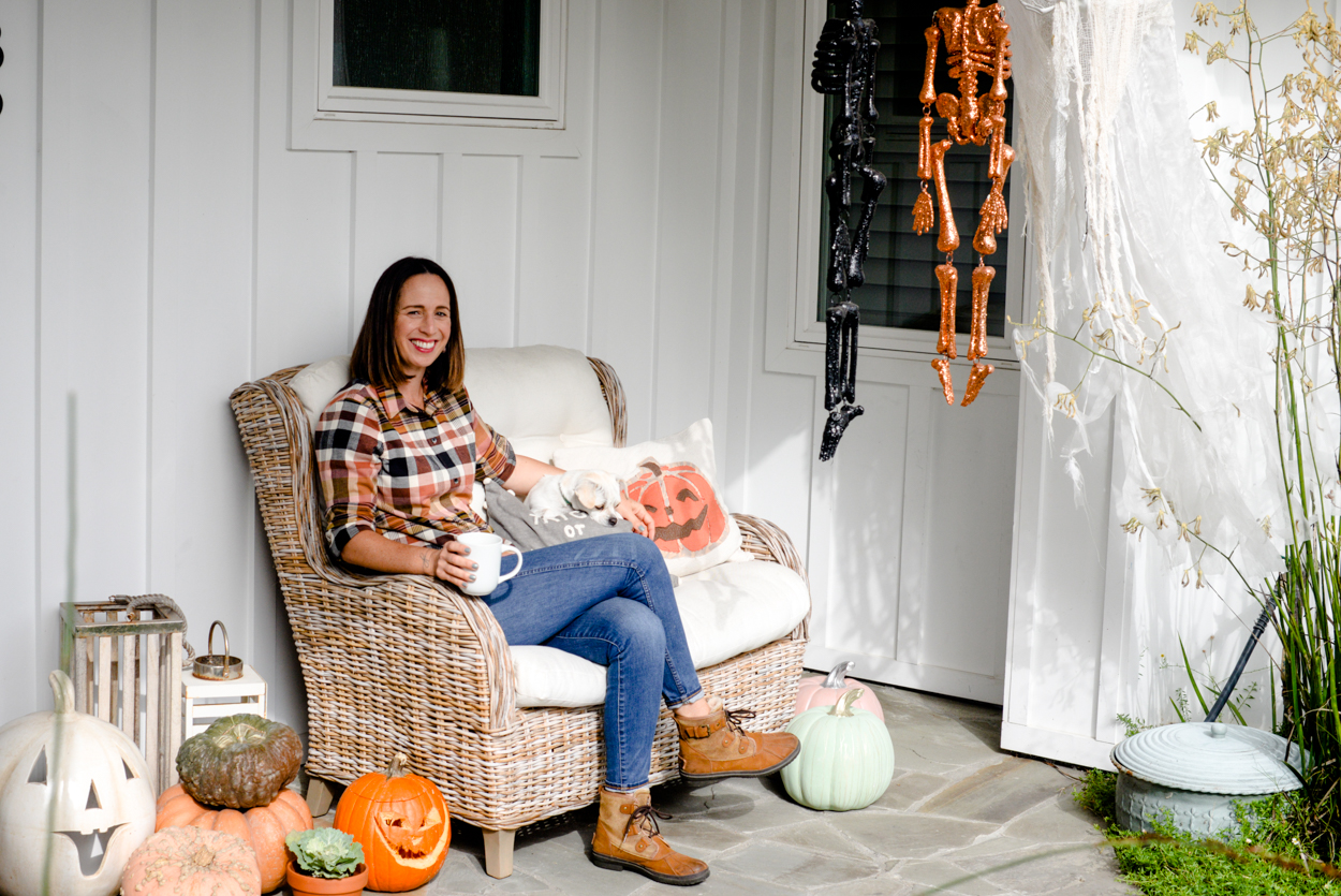 Woman with short brown hair wearing jeans and a plaid shirt sitting on a bench on a porch with a dog and Halloween decorations