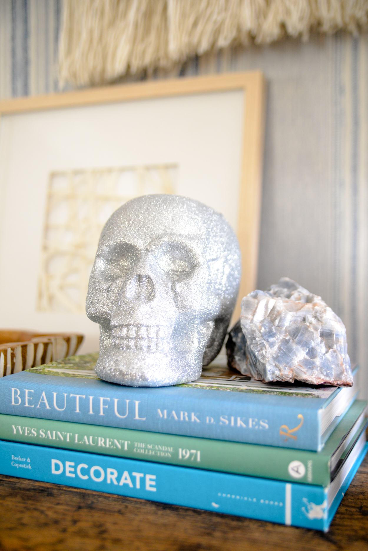 Silver glitter skull sitting on a stack of blue books