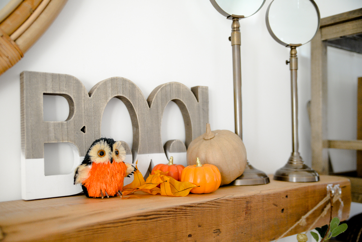 Wooden boo sign and paper pumpkin and orange owl sitting on a rustic wooden mantel