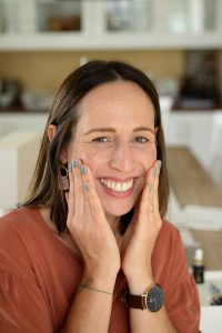 woman with brown hair smiling as she applies lotion to her face