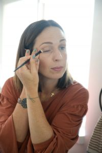 Woman with brown hair applying eye shadow in mirror