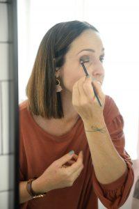 Woman with brown hair applying eyeshadow in mirror