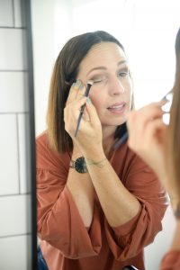 woman with brown hair applying eyeshadow in mirror