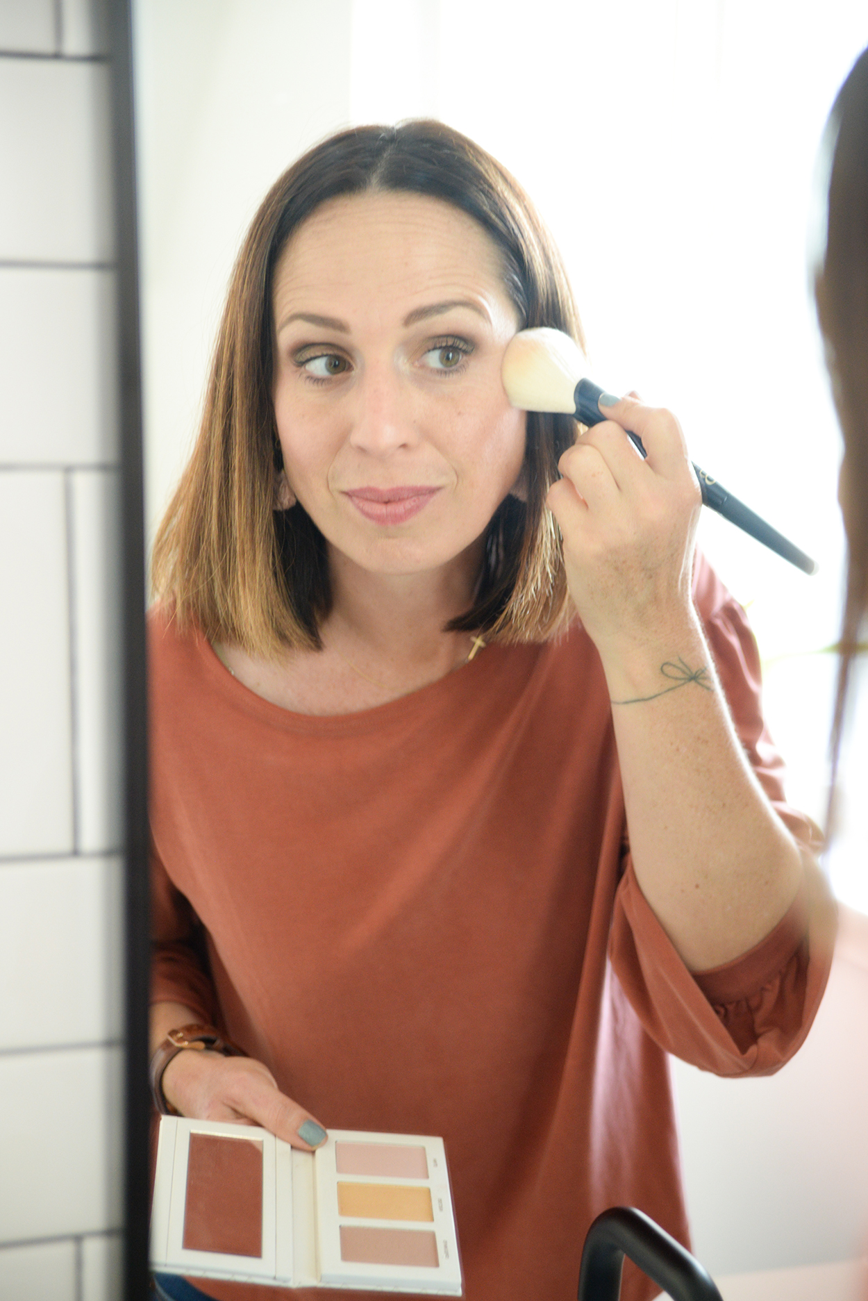 Woman with brown hair applying blush in mirror