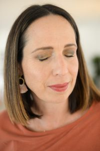 woman with brown hair and eyes closed showing eyeshadow colors