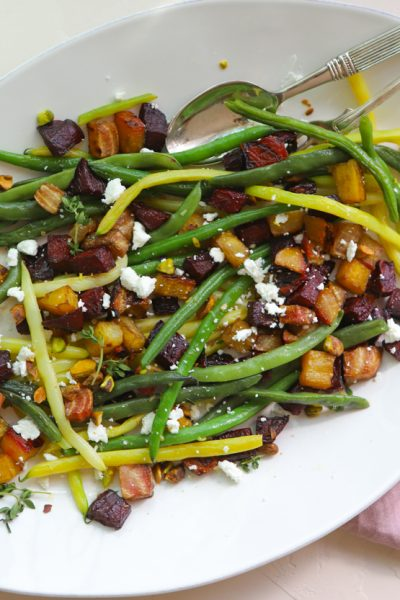 green beans and roasted beets sprinkled with goat cheese and pistachios on a white platter against a white backdrop