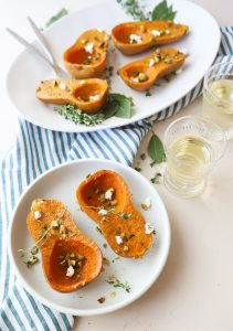 honeynut squash on a white plate sprinkled with goat cheese and pistachios