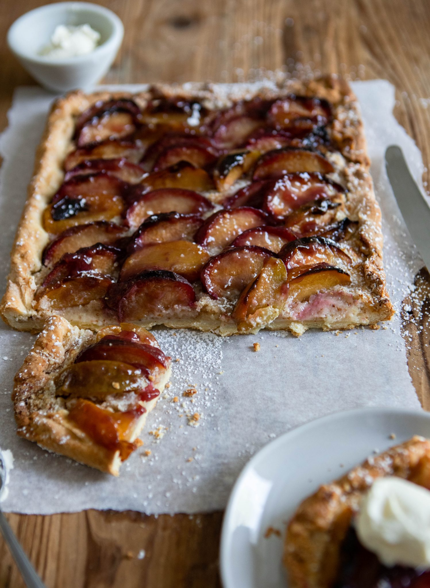 head on shot of a piece of rustic plum tart on a round white plate