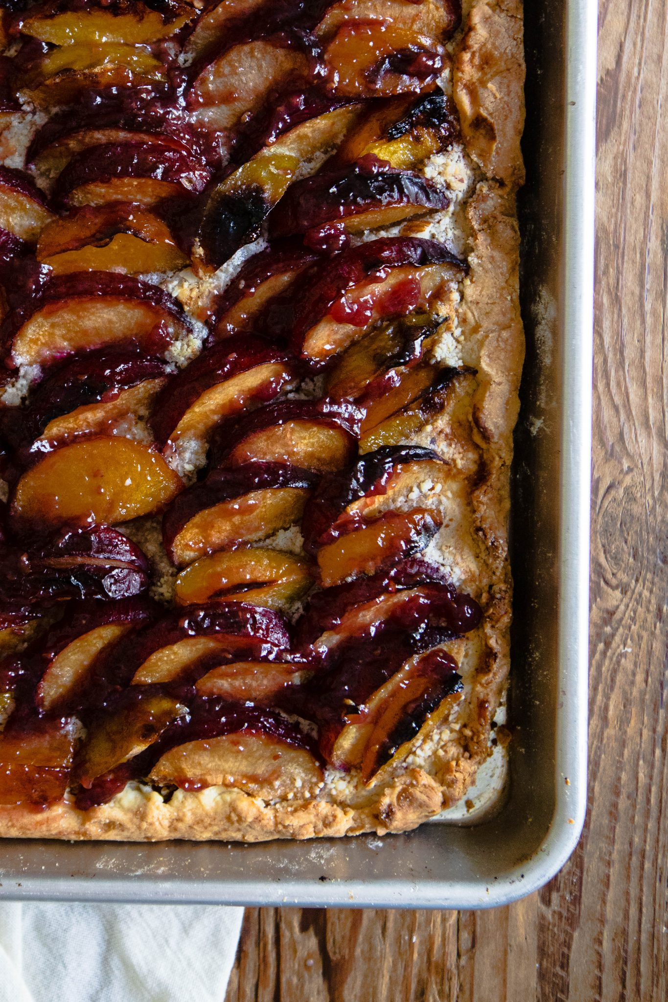 close up of rustic plum tart out of the oven, sitting in a baking pan against a wood backdrop