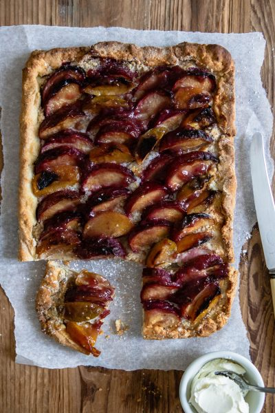 close up of a plum tart with a knife on top of parchment paper against a wooden backdrop